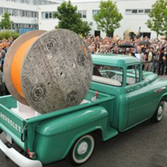 A green vintage car loaded with a huge cable spool is standing in front of a crowd