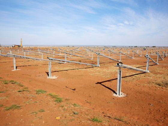 Ein großes Feld mit Solaranlagen für Solarenergie im Bau auf roter Erde
