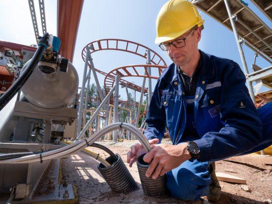 Ein Bauarbeiter verkabelt eine Achterbahn mit Kabeln von LAPP