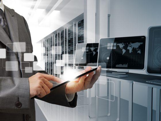 Ein Mann in Anzug bedient ein Tablet. Er ist umgeben von Computern und Schaltschränken