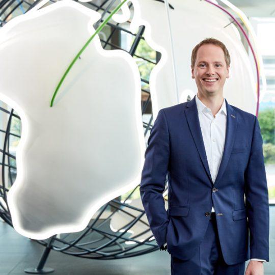 Matthias Lapp steht vor einer verkabelten Weltkugel