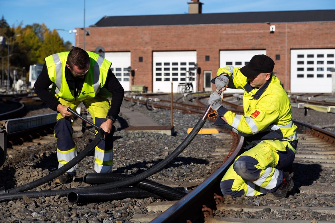 Workers are treating a cable in the track bed of the Oslo subway
