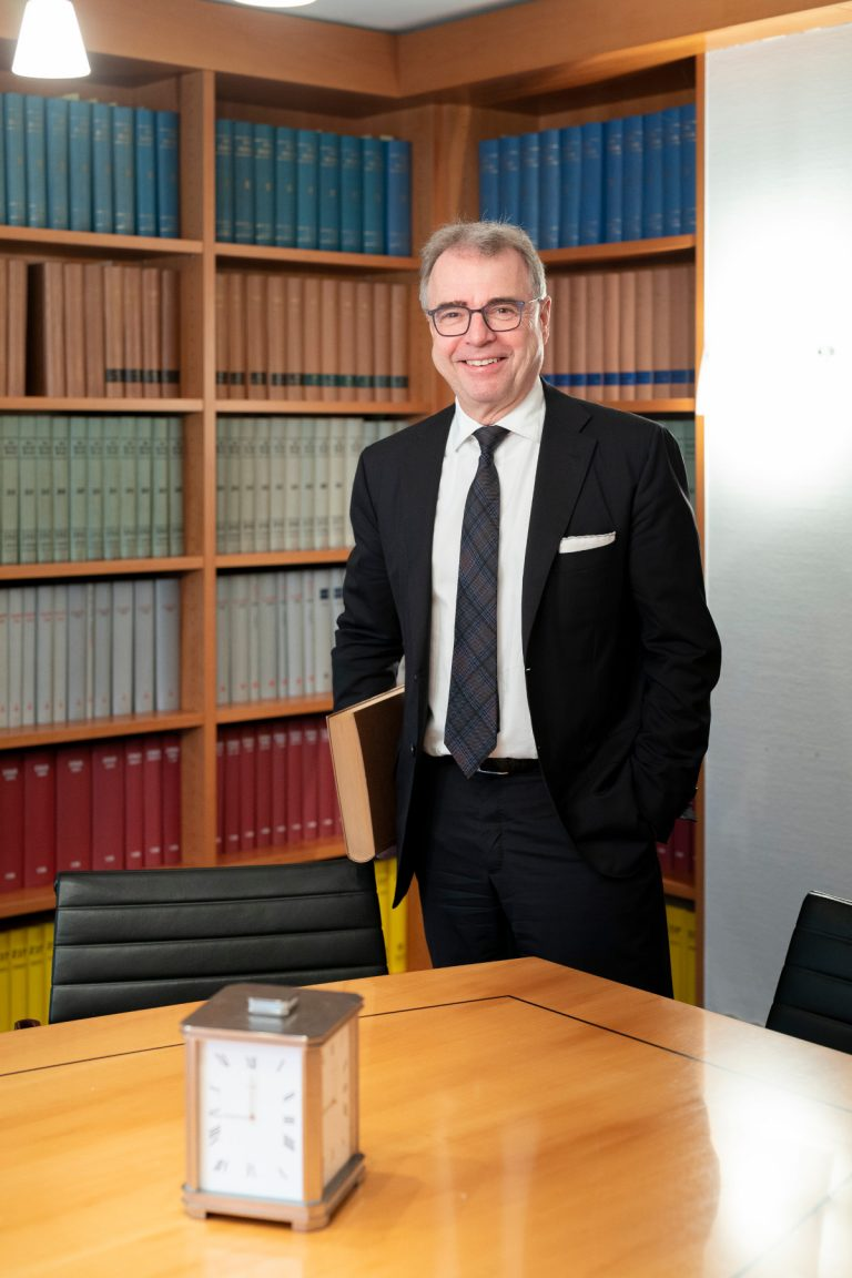 Rainer Kirchdörfer in front of a bookshelf is an expert in generational change in a family business