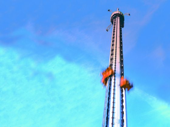 A free fall tower in action in front of blue sky