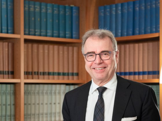 The lawyer Rainer Kirchdörfer in front of a bookshelf