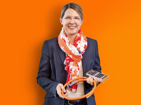 A smiling business woman holds a cable in her hand.