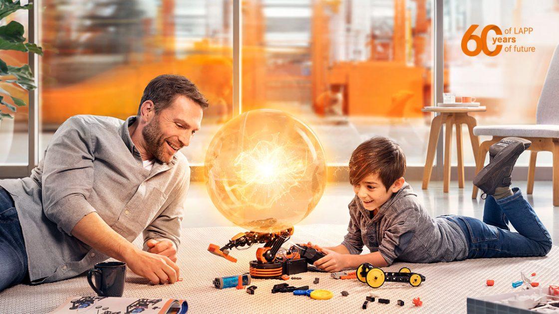Vater und Sohn bauen an einem Roboter, im Hintergrund eine moderne Fertigungshalle