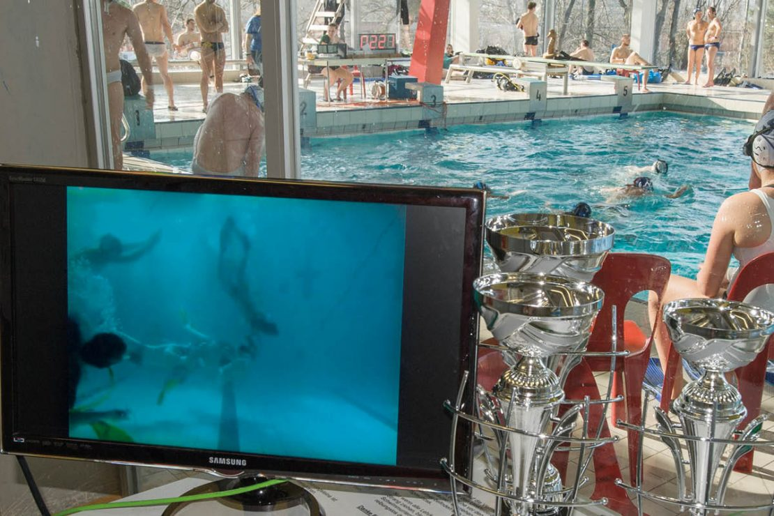 The video transmission of the underwater rugby tournament is shown on a monitor.