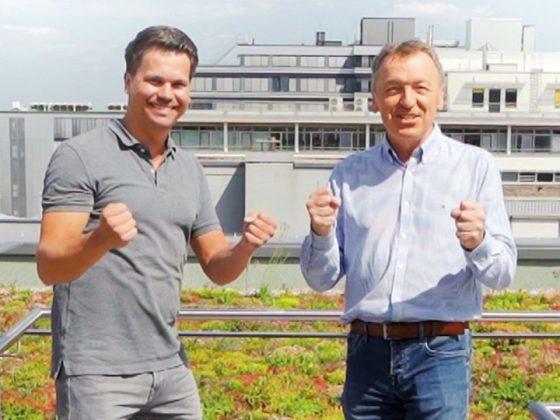 Die LAPP Produktmanager Benjamin Rentschler (links) und Daniel Müller (rechts) entwickelten die runde SKINTOP® MULTI-M. Sie stehen auf dem Dach von LAPP und freuen sich.
