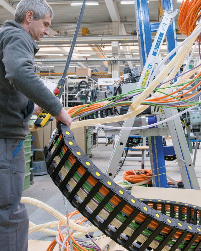 A Bystronic glass employee unpacks a SILVYN® CHAIN energy chain from LAPP.