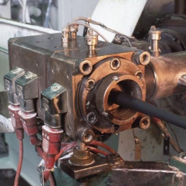 Das Bild zeigt eine Extrusionanlage, in der in einem Arbeitsgang ein antistatische Außenmantel auf eine Kabel aufgebracht wird.