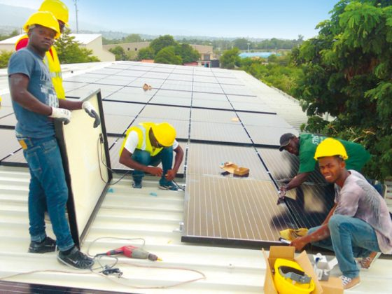 "You can see workers on a roof assembling the ""Solar Smart Grid"" modules."