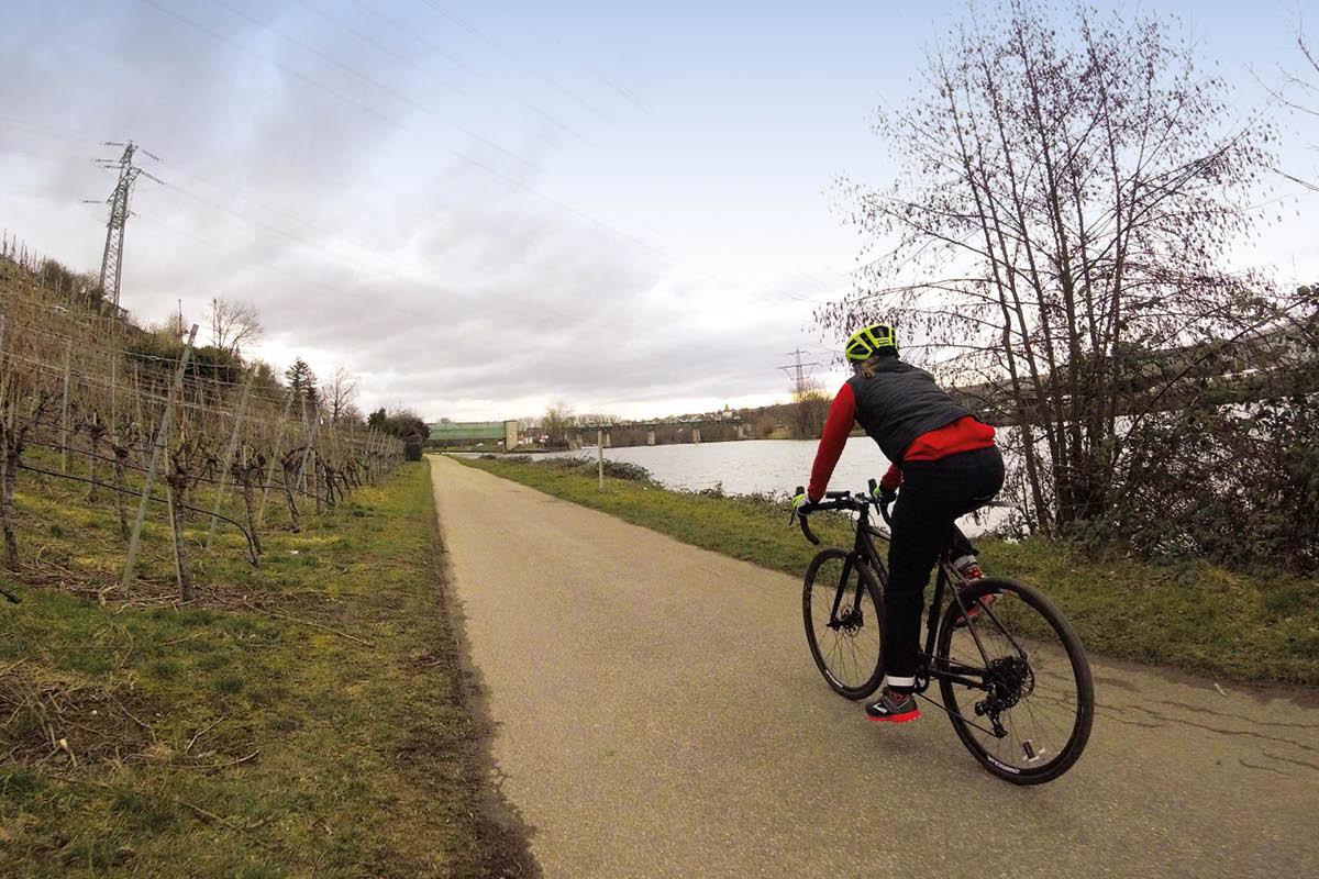 Auf dem Bild sieht man einen Radfahrerin im Gelände radfahren.