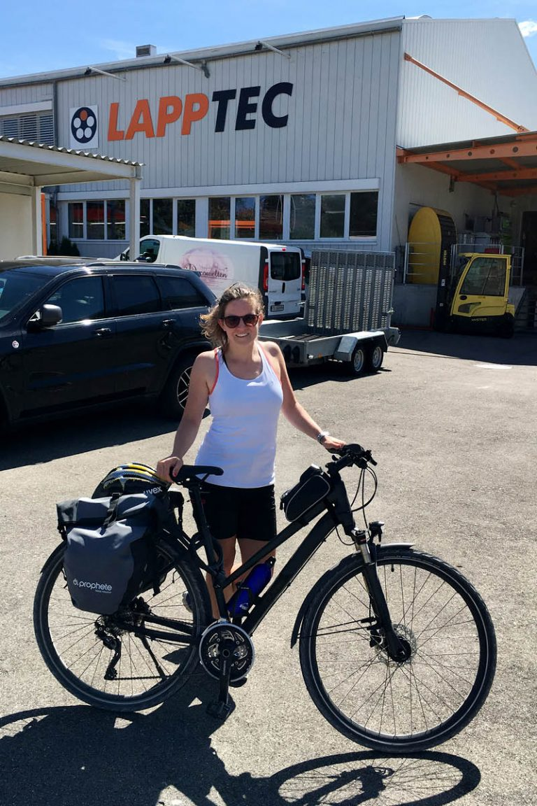 In this picture you can see a LAPP employee with a bike in front of LAPPTEC.