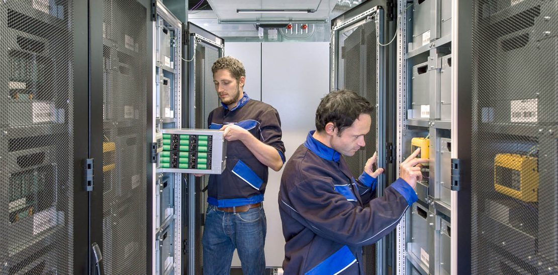 In the picture you can see two employees working in a server room.