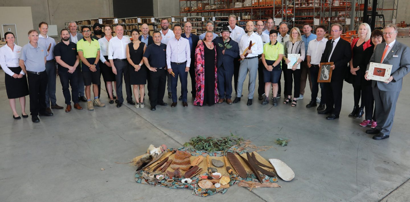 The picture shows the LAPP Australia team with Andreas and Alexander Lapp in the factory hall.