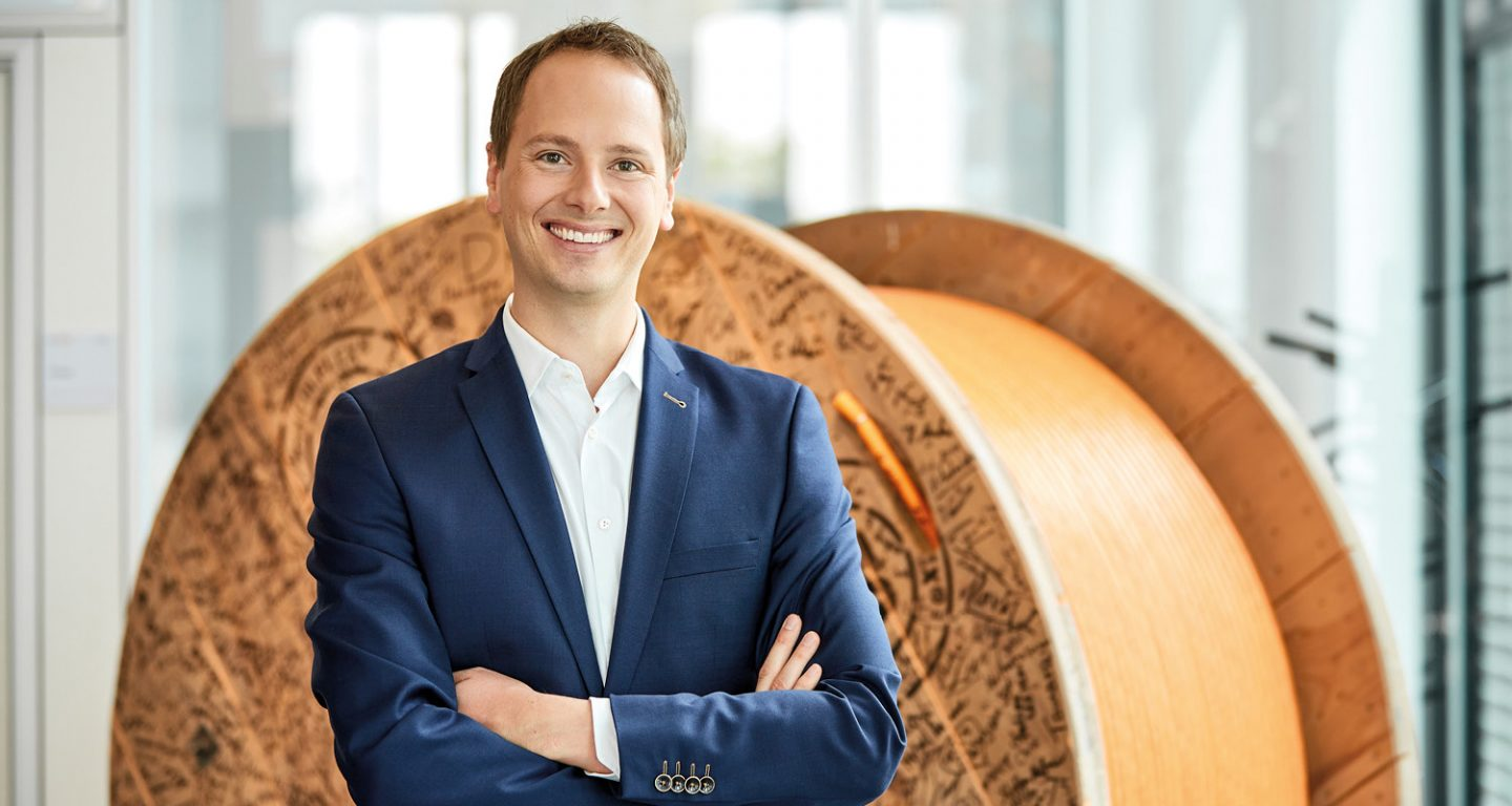 Matthias Lapp, CEO & Managing Director of U.I. LAPP GmbH stands in front of a cable drum.