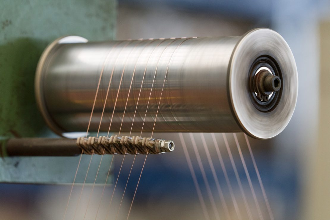 The picture shows the manufacturing process for twisting a cable.