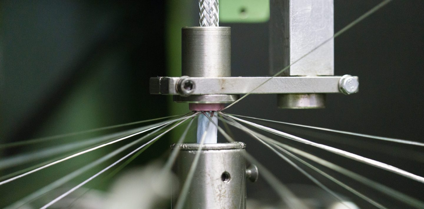 The picture shows the manufacturing process for the shielding of a cable.