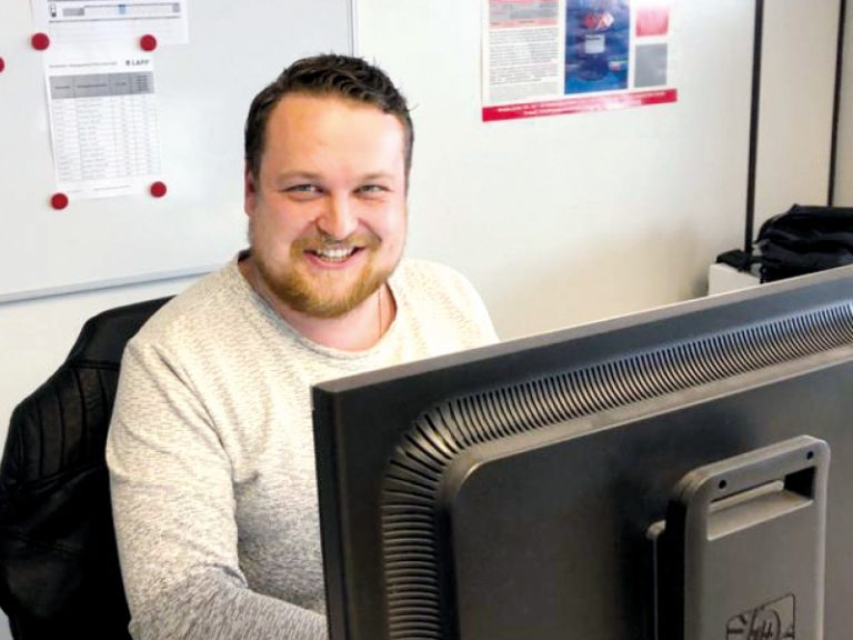 The picture shows Alexander Kraus, Material Management employee at Lapp GmbH Kabelwerke, at work in front of the computer.