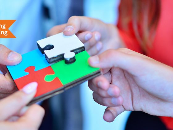 The picture shows the hands of four people putting together a puzzle with four pieces.