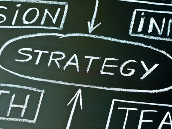 The picture shows a graphic with the word Strategy drawn in chalk on a blackboard in relation to the words: Vison, Innovation, Growth, Team.