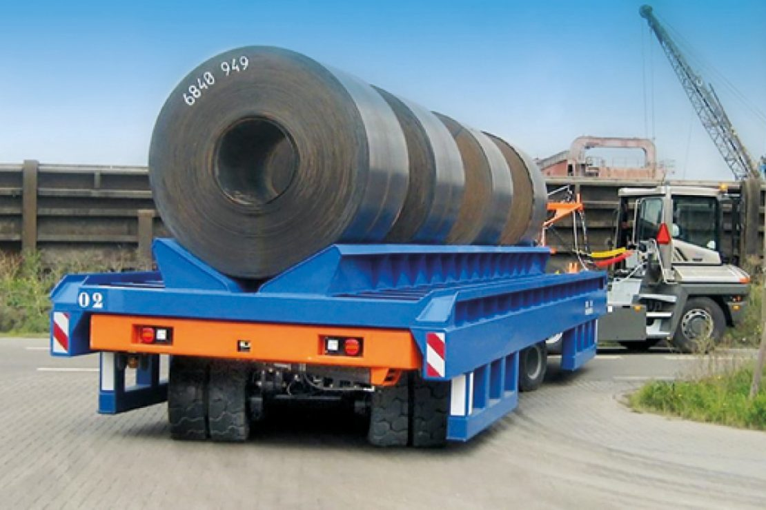 The picture shows a truck for heavy goods with a cassette on top, loaded with large cable drums.