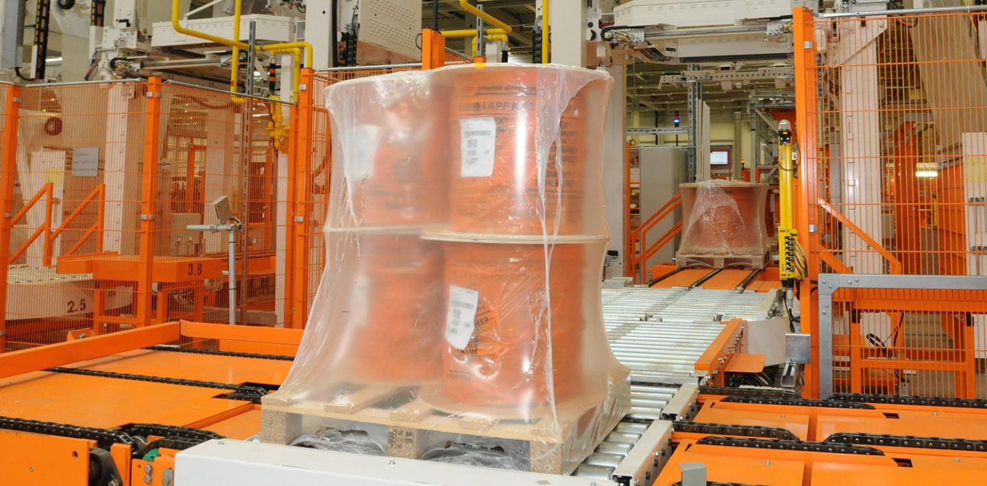 The picture shows a packaging line with a film-shrunk cable drum.